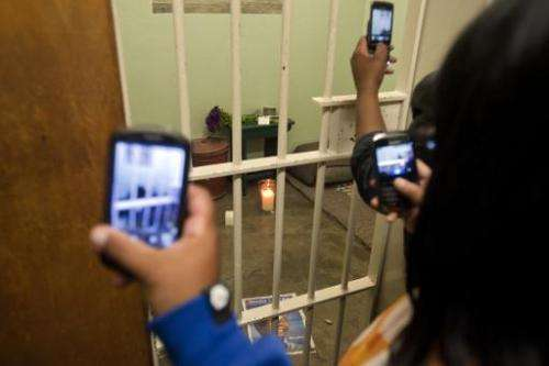 People take pictures of Nelson Mandela's former cell at Robben Island on December 13 2013