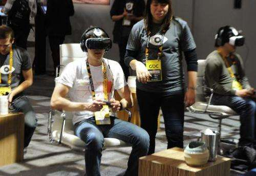 People try out a virtual reality system at the Oculus booth during the Game Developers Conference in San Francisco, California o