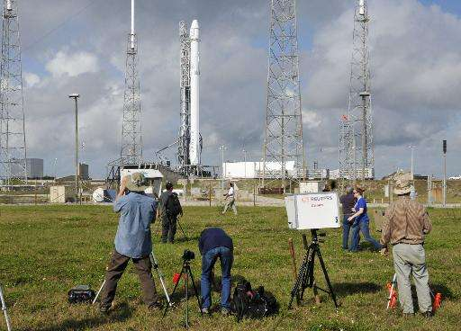 Photographers look on at the SpaceX Falcon 9 rocket, as they wait for the launch in Cape Canaveral, Florida on April 13, 2015