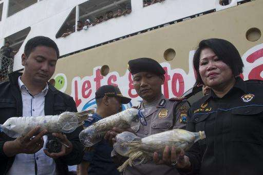 Police and customs officials hold rare Indonesian yellow-crested cockatoos, jammed inside plastic water bottles, confiscated fro
