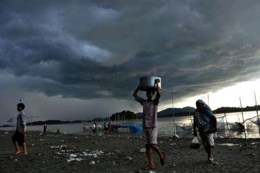 Rain clouds loom over the Brahmaputra river in Guwahati, capital of northeastern Assam state, India on August 27, 2013