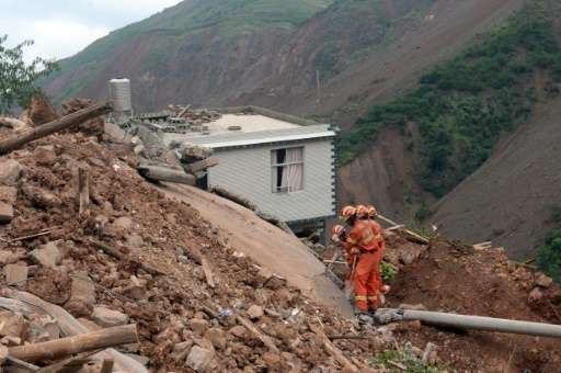 Rescue workers searching for victims in the debris in Ganjiazhai village, buried by landslide during the earthquake, in Longtous