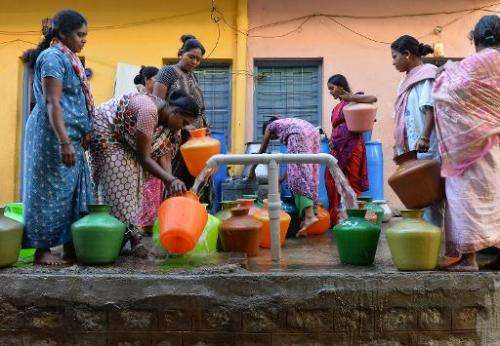 Residents in Bangalore wait to collect drinking water in plastic pots for their households on March 18, 2015