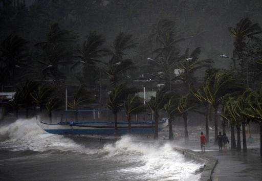 Residents walk past high waves brought about by strong winds, hours before Typhoon Hagupit passes near the city of Legazpi on De