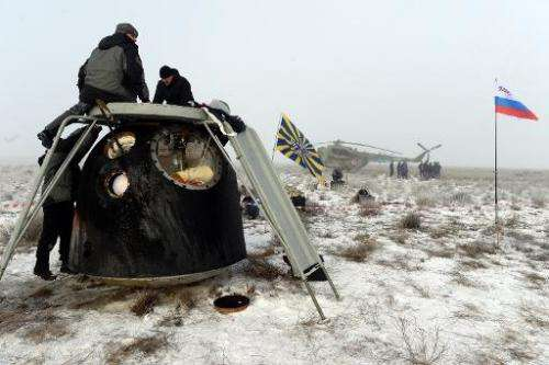 Russia's space agency ground personnel check Soyuz TMA-14M capsule shortly after the landing in a remote area outside the town o