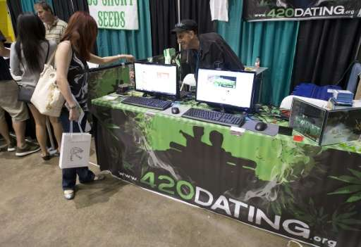 Scott Migdol talks with a visitor about his online dating website for marijuana users called 420Dating.com, at the HempCon medic