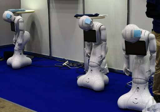 """Softbank's """"Pepper"""" humanoid robots 'rest' before the International Robot Exhibition in Tokyo, on December 2, 2015"""