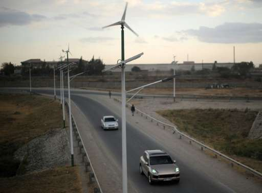 Street lamps powered by wind and solar energy line the side of a road leading from Athi-river town in Machakos county, approxima