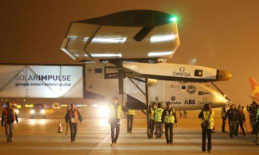 Team members walk next to the aircraft Solar Impulse 2, as Swiss pilot Bertrand Piccard taxis the plane after landing at Nanjing