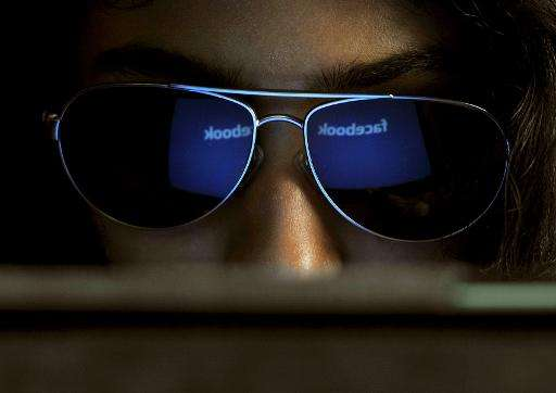 The 'Facebook' logo is reflected in an Indian woman's sunglasses as she browses on a tablet in Bangalore on May 15, 2012