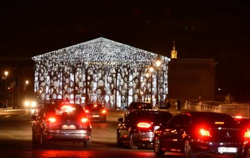 The images of more than 500 people are projected on the facade of the French National Assembly building during the 2015 UN Clima