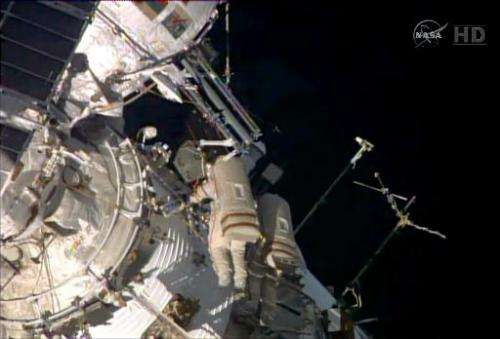 This October 22, 2014 image from NASA TV shows Russian's Commander Max Suraev (L) and Flight Engineer Alexander Samokutyaev work