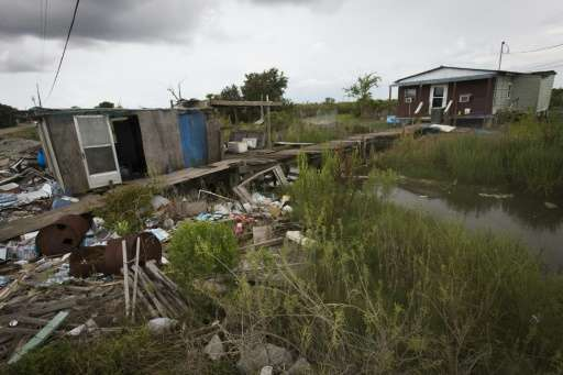 Trash is scattered in front of a house on the Isle de Jean Charles, Louisiana