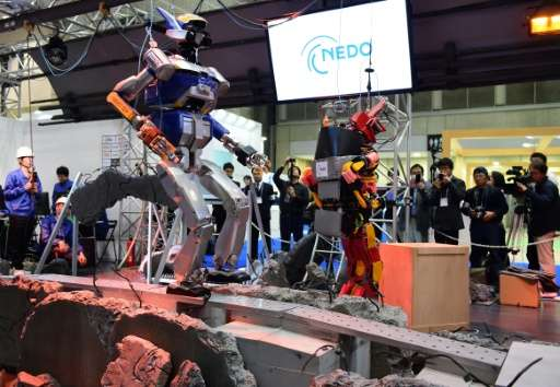 Two humanoid robots walk over mock debris to show their disaster-response abilities at the International Robot Exhibition in Tok