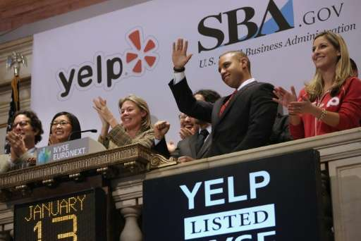Yelp executives wave after ringing the closing bell of the New York Stock Exchange at the end of a trading day, in 2014