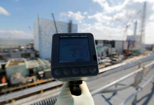 A TEPCO employee measures the radiation in front of the No. 2 and No.3 reactor buildings during a press tour at the Fukushima Da