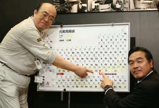 Japanese scientist Kosuke Morita (left) and Science Minister Hiroshi Hase point to the periodic table displaying the new element
