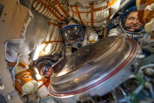 NASA astronaut Jeff Williams (L) and Russian cosmonauts Alexey Ovchinin (C) and Oleg Skripochka inside their Soyuz spacecraft mo