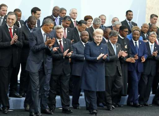 US President Barack Obama (2nd L) applauds after a family photo with fellow world leaders during the opening day of the World Cl