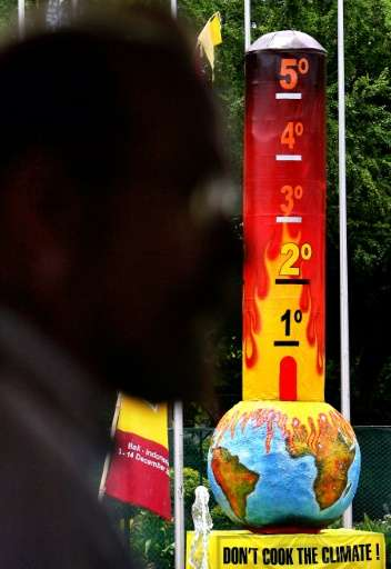A delegate walks past a huge paper made thermometer ontop of a globe set up by Greenpeace