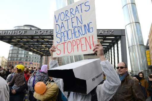 """A demonstrator holds up a poster reading, """"Stop data preservation"""" during a protest in Berlin on April 18, 2015"""