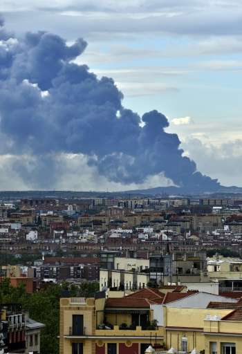 A huge column of smoke caused by a fire at a tyre dump near the town of Sesena pictured from the Almudena cathedral in Madrid on