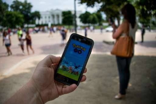 A man holds up his cell phone with a screen shot of the Pokemon Go game in front of the White House on July 12, 2016