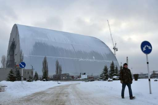 A man walks past the Chernobyl New Safe Confinement structure (NSC) under construction in Chernobyl, Ukraine on January 22, 2016