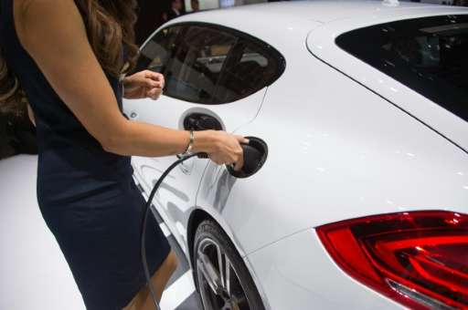 A model inserts the electric charger into the Porsche Panamera S E-Hybrid at the North American International Auto Show in Detro