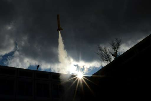 A model of a rocket blasts off from a courtyard of the International Space School in Baikonur, near the Russian-leased cosmodrom