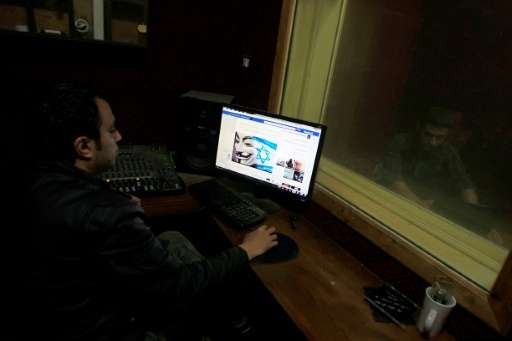 """A Palestinian man looks at Facebook page with a picture depicting the """"#Op_Israel"""" campaign launched by the activist g"""