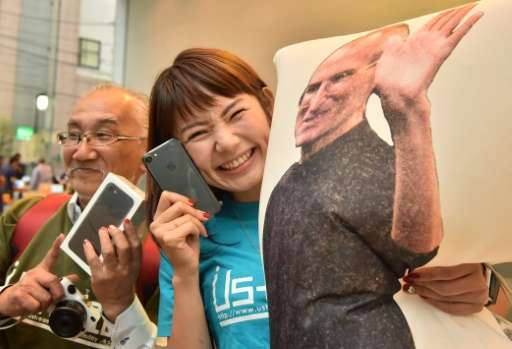 Apple fanatics display their newly bought iPhone 7 smartphones at the company's flagship store in Tokyo, on September 16, 2016