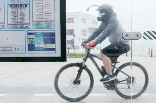 A QR code is pictured on a public bus stop as a cyclist rides past in the northern Spanish city of Santander