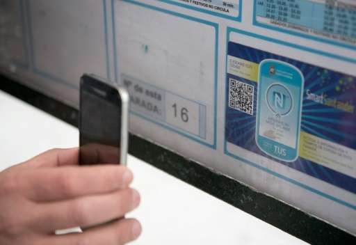 A resident uses a mobile phone to read a QR code on a public bus stop in Santander