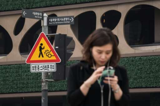 A sign advising pedestrians of the dangers of using smartphones while walking is displayed at an intersection in central Seoul o