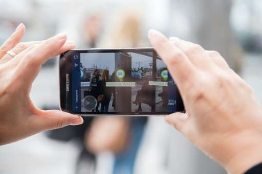 A tourist uses a mobile phone app to look for information about the northern Spanish city of Santander