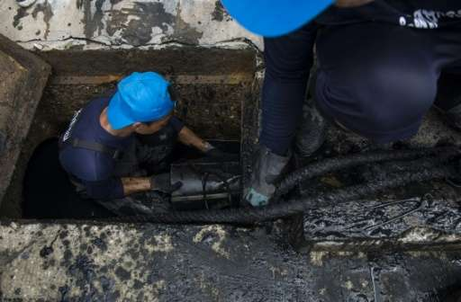 A volunteering prisoner pushes a metal bucket into place inside a drain to dredge it from sewage and plastic waste in the outski