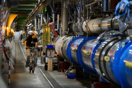 A worker rides his bicycle in a tunnel of the European Organisation for Nuclear Research (CERN) Large Hadron Collider during mai