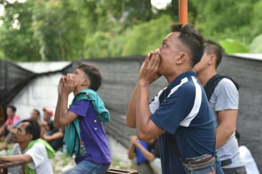 """Bird owners shout during a bird singing contest in Indonesia, where a nationwide craze known as """"chirping mania"""" is bl"""