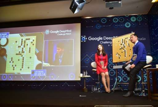 Commentators sit next to a big screen showing the match between Lee Se-Dol and AlphaGo in Seoul on March 9, 2016