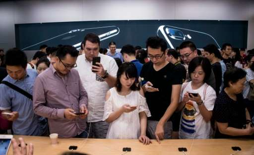 Customers check out the new iPhone 7 at an Apple store in Shanghai, on September 16, 2016