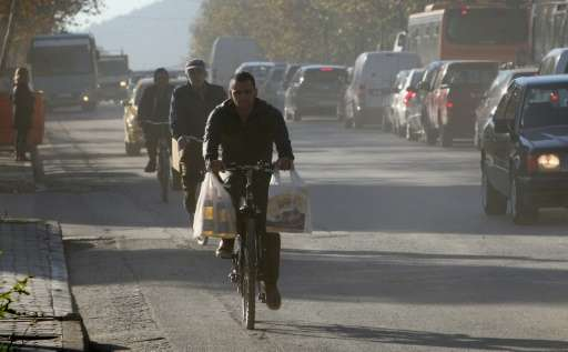 Cyclists travel in heavy pollution on the noisy and congested streets of Tirana