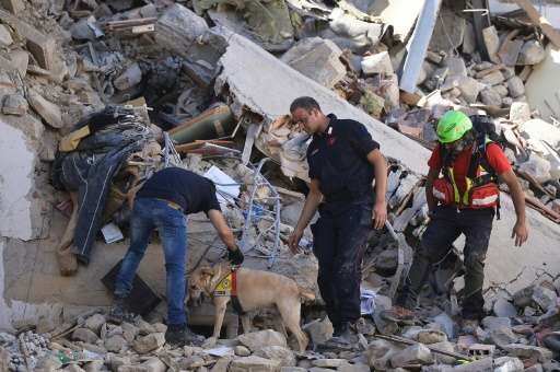 Firemen and rescuers search destroyed buildings in Amatrice, central Italy following the quake early on August 24, 2016