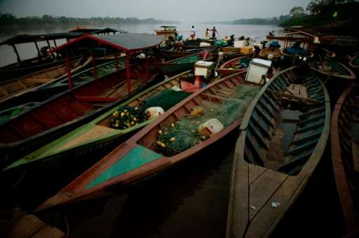 Fishing boats lie at sundown tied up on the shore at a port in the Puerto Maldonado city on the banks of the Madre de Dios River