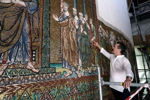 Giammarco Piacenti, CEO of the Piacenti restoration company, inspects a renovated mosaic wall inside the Church of the Nativity