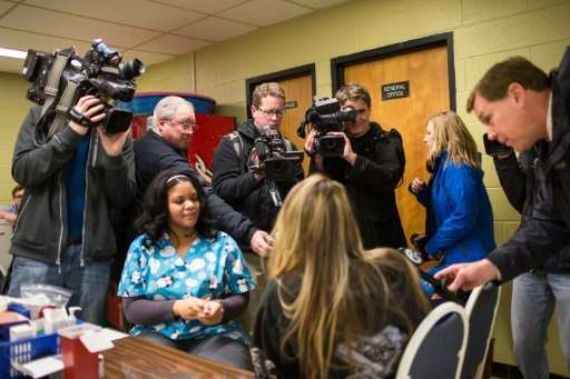 Members of the media surround a family as their child is screened for lead exposure at Eisenhower Elementary School in Flint, Mi