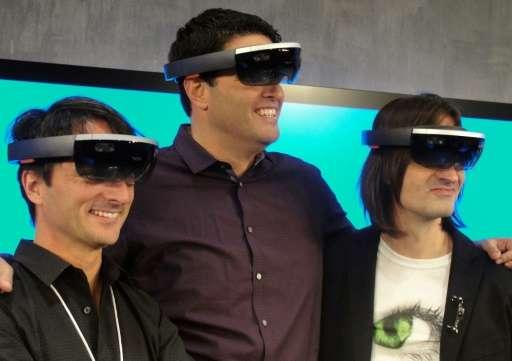 Microsoft executives Joe Belfiore (L), Terry Myerson (C) and Alex Kipman (R) wear HoloLens eyewear that overlays 3D images on th