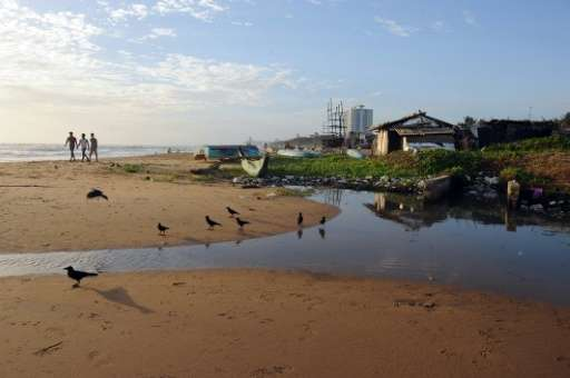 People are seen walking past an open sewer drain off Mount Lavinia beach, on the outskirts of Colombo