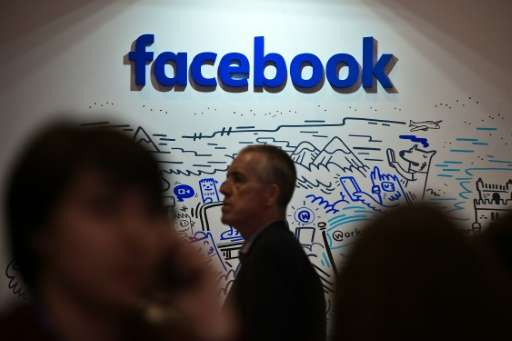People pass by the stand of Facebook during the Web Summit at Parque das Nacoes, in Lisbon on November 9, 2016