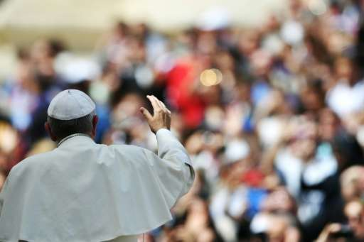 Pope Francis waves to pilgrims gathered in St Peter's Square at the end of his weekly general audience at the Vatican on April 6